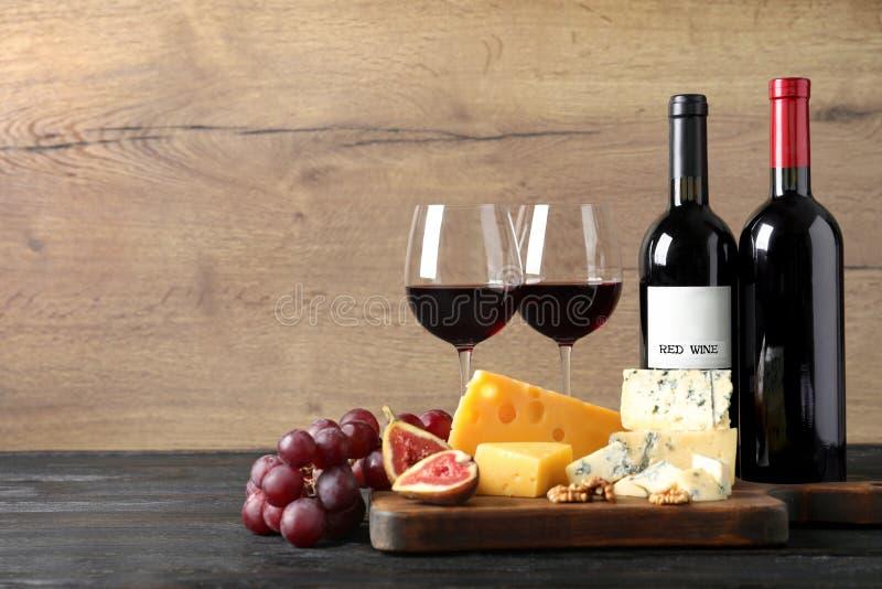 Queijos, frutos e vinho deliciosos diferentes na tabela contra o fundo de madeira, espaço para foto de stock royalty free