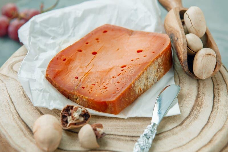 Queijos picantes das guloseimas O queijo Cheddar vermelho, em um fundo de madeira textured bonito com porcas de noz-pecã é um pet fotografia de stock