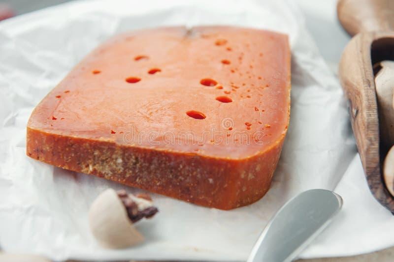 Queijos picantes das guloseimas O queijo Cheddar vermelho, em um fundo de madeira textured bonito com porcas de noz-pecã é um pet fotos de stock royalty free