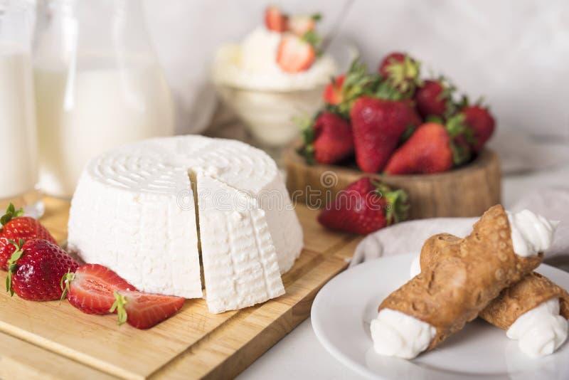 Queijos sortidos na placa de madeira Camembert, queijo com oídio azul, Gouda, queijo duro, morangos, bolo foto de stock