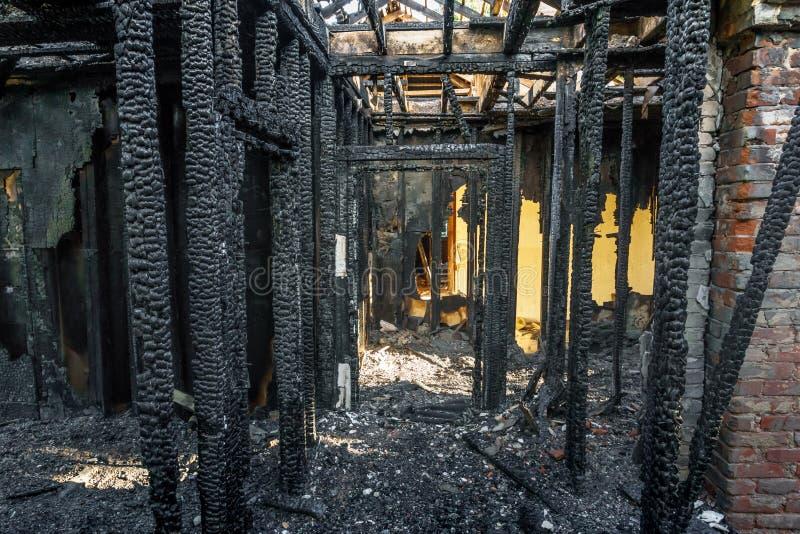 Queimado abaixo da casa de apartamento de madeira, paredes carbonizadas, telhado queimado imagens de stock