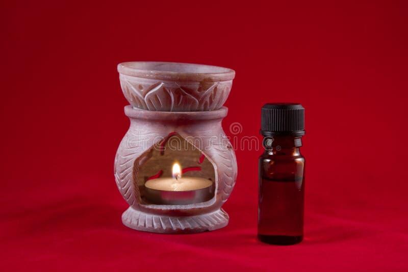 Queimador de petróleo com o frasco no fundo vermelho fotografia de stock