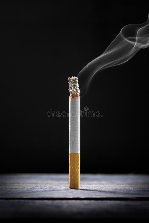 Queimadura de cigarro na tabela de madeira fotografia de stock