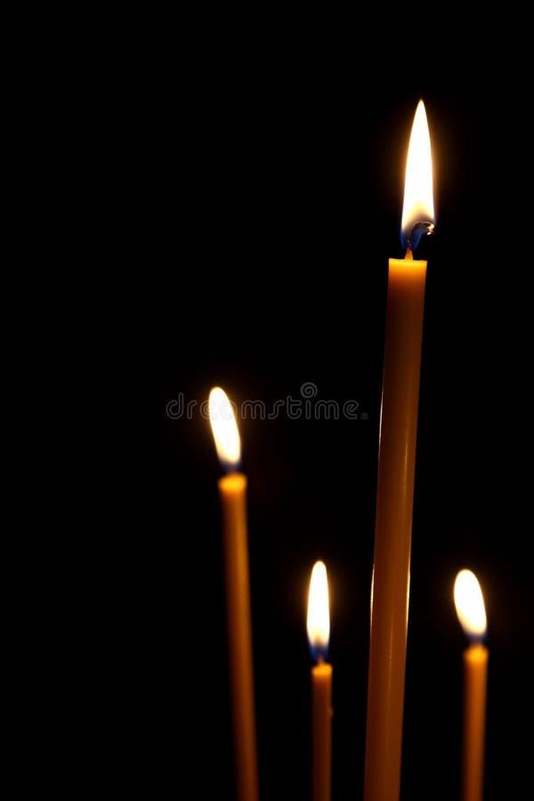 Queimadura na obscuridade para quatro velas da cera fotografia de stock