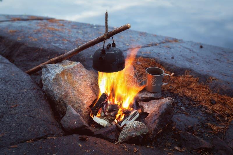 Queimando fogo na natureza perto do lago A fogueira queima à noite Descanse perto do fogo Bonfire imagem de stock