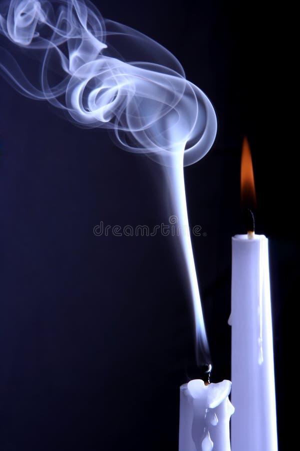 Queimando-se e extinto as velas no fundo escuro fotos de stock
