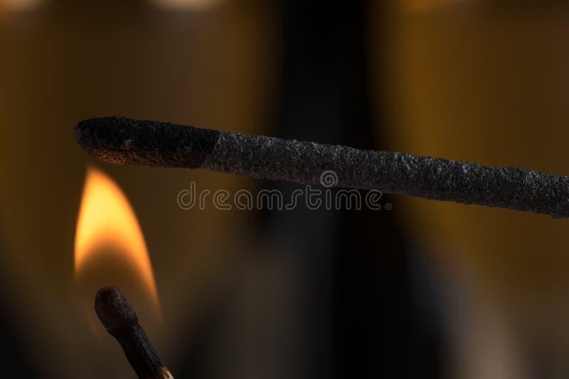 Queimando um chuveirinho com um matchstick Aqui está no fogo imagens de stock royalty free