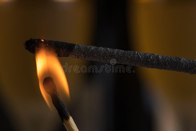 Queimando um chuveirinho com um matchstick Aqui está no fogo imagem de stock