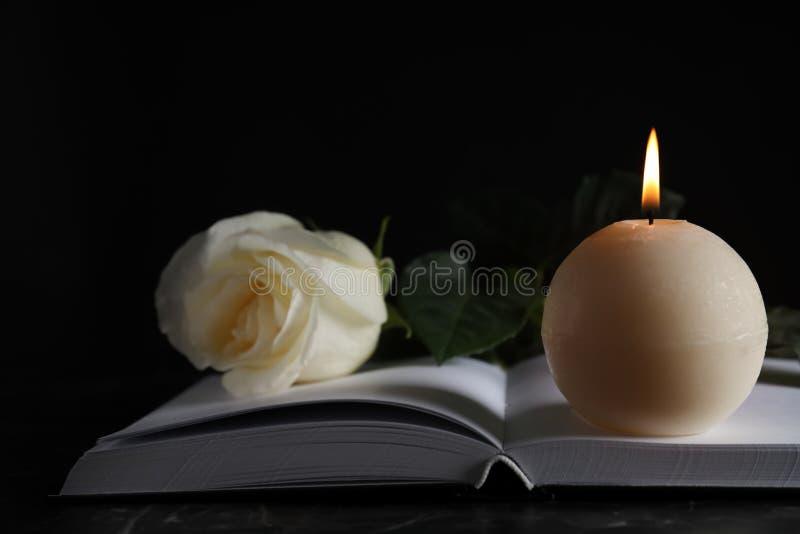 Queimando vela, branco e livro sobre a mesa na escuridão, fechar Símbolo funerário imagens de stock royalty free