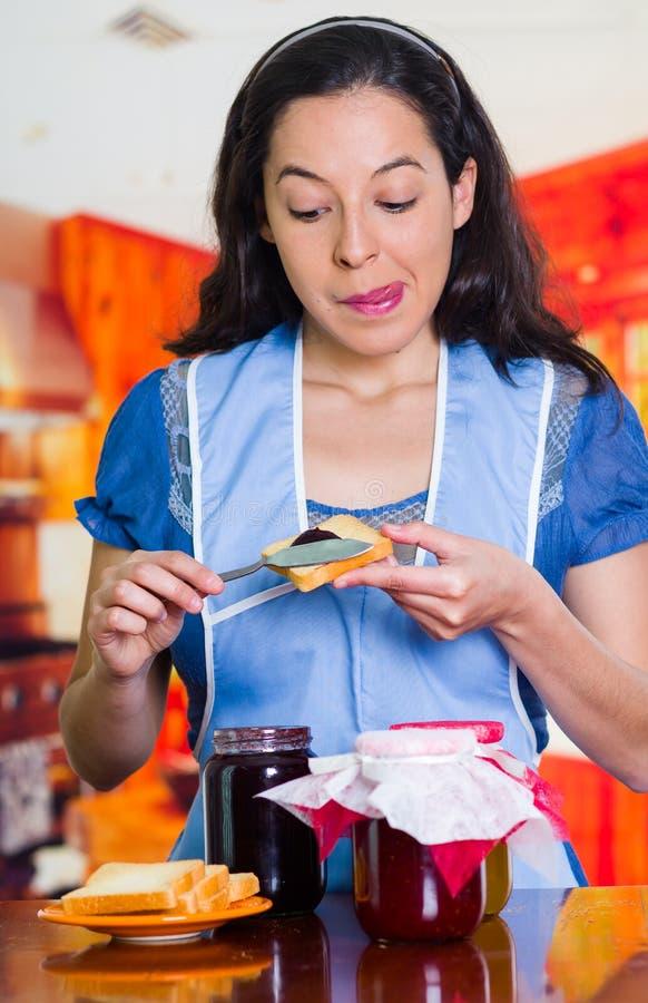 Queira comer a cara de uma mulher que põe algum doce em seus brinde, doces diferentes sobre uma tabela e sabores fotografia de stock royalty free