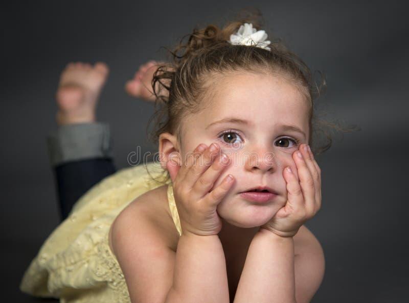 Queixo de encontro da menina da criança de dois anos nas mãos fotos de stock royalty free