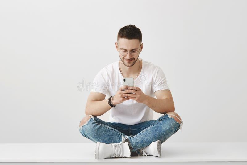 Quel APP impressionnant j'ai téléchargé Le studio a tiré du jeune collègue attirant s'asseyant dans l'équipement à la mode sur le photos stock