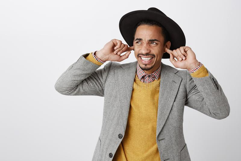 Quelqu'un arrêtent la musique bruyante Tir de studio de jeune ami à la peau foncée contrarié contrarié dans le chapeau noir et la image stock