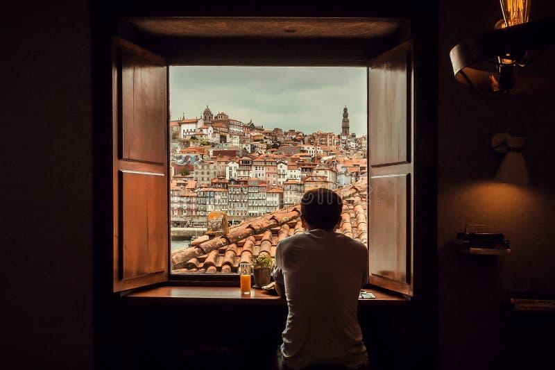 Quelqu'un paysage urbain de observation par la fenêtre, le vieux paysage de ville avec des toits et la rivière images libres de droits