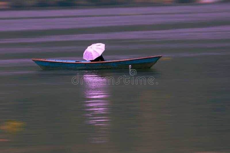 Quelqu'un s'asseyant avec le parapluie dans le bateau coloré dans le lac image stock