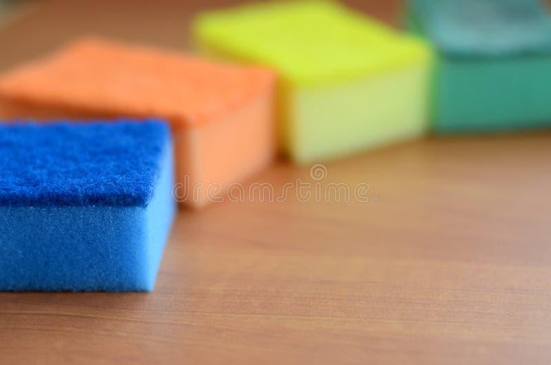 Quelques éponges de cuisine se trouvent sur une partie supérieure du comptoir en bois de cuisine Les objets colorés pour les plat images stock