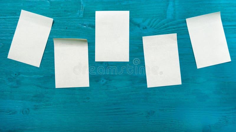 Quelques autocollants jaunes collés sur un fond en bois bleu Le concept des rappels, bureau images libres de droits