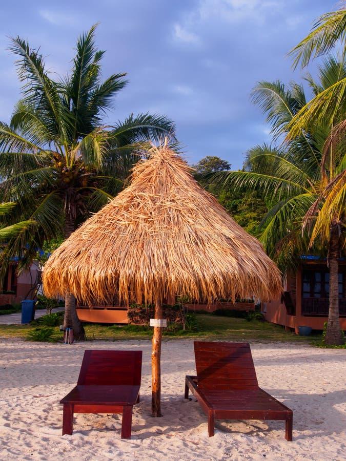 Quelques banc sur la plage avec le parapluie de chaume contre le ciel bleu photos libres de droits