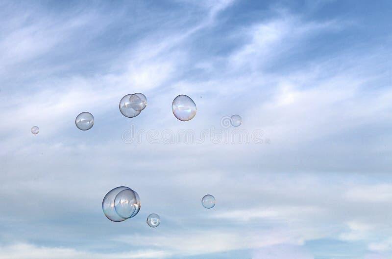 Quelques bulles de savon volent contre le ciel image stock