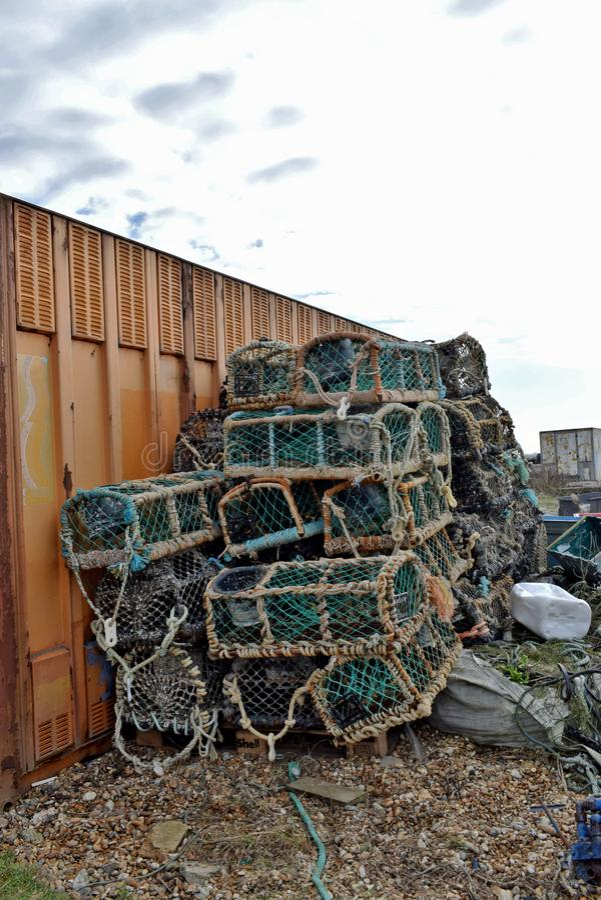 Quelques casiers enveloppés en filet de pêche empilé contre un grand conteneur image libre de droits