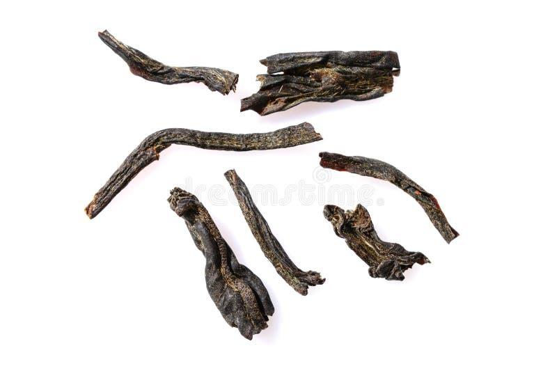 Quelques feuilles de thé sèches de thé noir lâche indien de Darjeeling sur le fond blanc, fin, macro images stock