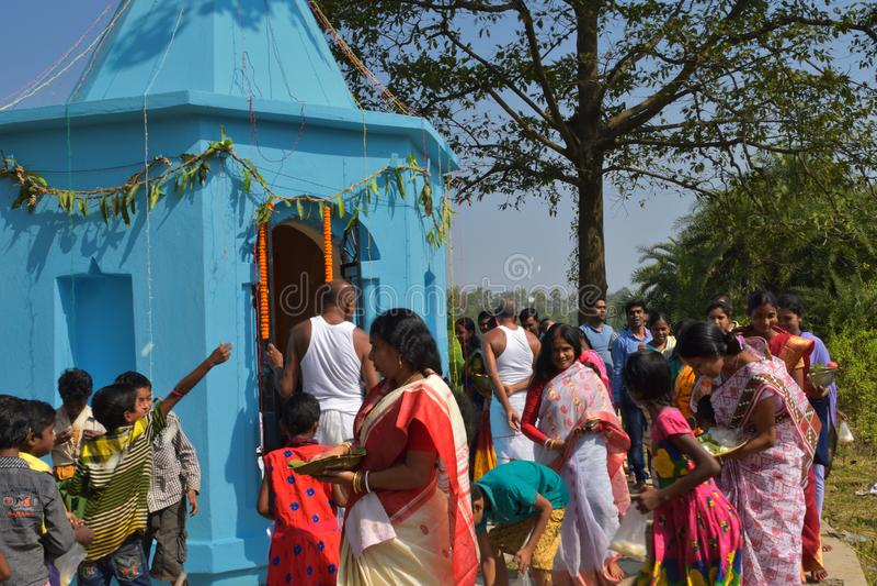 Quelques hommes et femmes effectuant des rituels de puja par la marche autour du temple et distribuant des bonbons aux enfants images libres de droits
