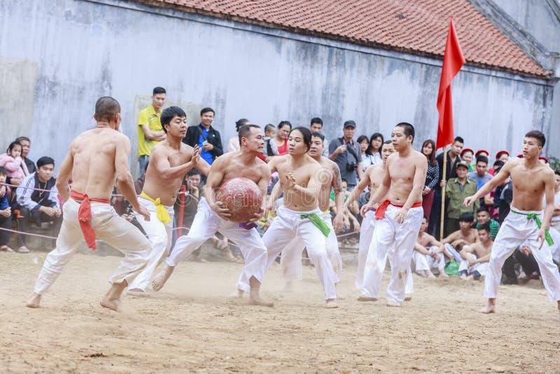 Quelques jeunes hommes jouent avec la boule en bois pendant année lunaire de festival la nouvelle à Hanoï, Vietnam le 27 janvier  photo libre de droits
