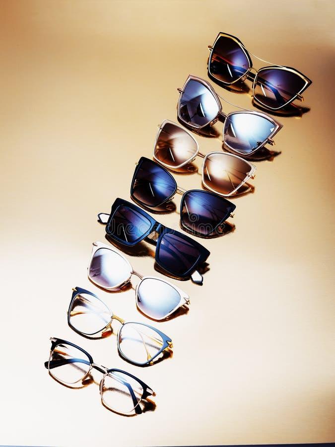Quelques lunettes de soleil d'?lite dans un cadre ? la mode moderne sur un fond d'or photographie stock libre de droits