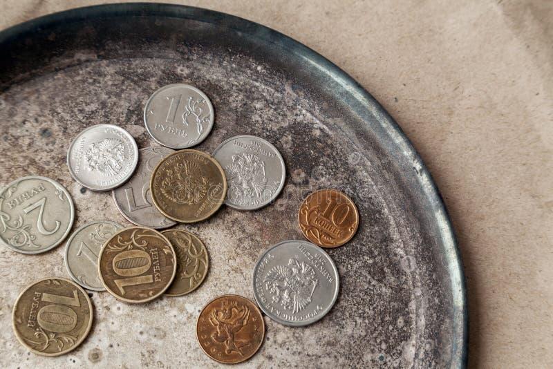 Quelques pièces de monnaie russes dispersées sur un plan rapproché de plat en métal photos stock