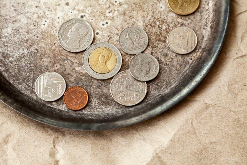 Quelques pièces de monnaie thaïlandaises dispersées sur un plan rapproché de plat en métal photographie stock
