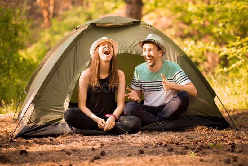Quelques touristes en temps de hausse, s'asseyent et détendent en dehors de la tente, admirant le beau paysage de montagne image stock
