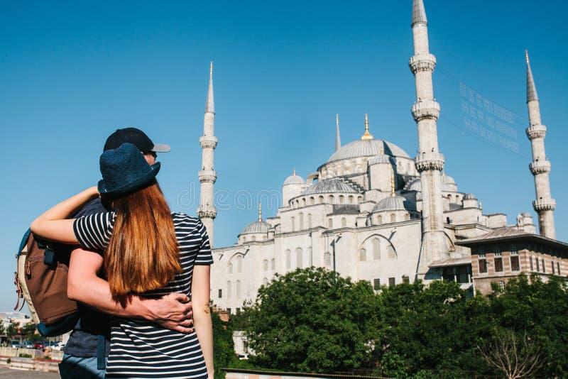 Quelques touristes un jeune homme et une jolie femme embrassent et regardent ensemble la mosquée bleue de renommée mondiale égale photo stock