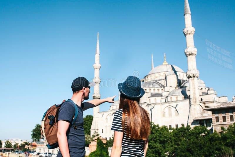 Quelques touristes un jeune homme et une jolie femme se tiennent à côté de la mosquée bleue de renommée mondiale Sultanahmet égal photos libres de droits
