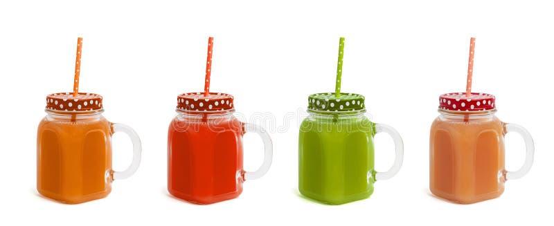 Quelques verres avec différents jus de couleurs sur un fond blanc Vue de côté image libre de droits