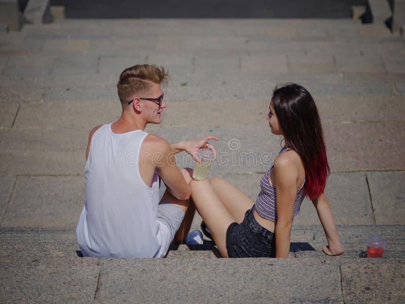 Quelques youngers se reposant et parlant entre eux sur le fond en pierre d'escaliers Relaxation, romance, dehors concept photographie stock libre de droits
