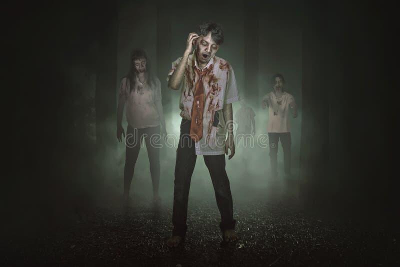Quelques zombis asiatiques fantasmagoriques avec le sang marchant autour images libres de droits