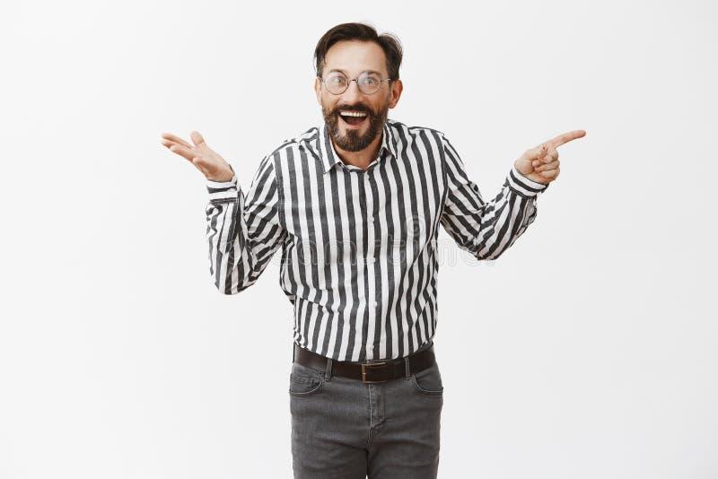 Quem poderia pensamento Homem maduro atrativo feliz e surpreendido impresso com a barba nos vidros e na camisa formal, apontando imagem de stock royalty free