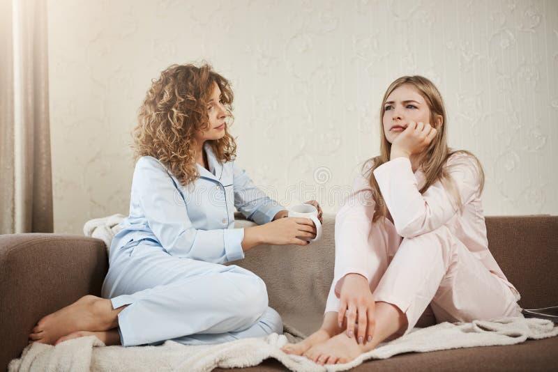 Quem precisam o psicólogo quando você tiver o melhor amigo Duas mulheres que sentam-se no sofá no nightwear na sala acolhedor, di fotos de stock