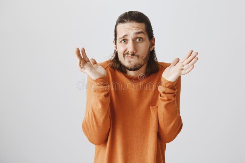 Quem se importa, eu sou indiferente Indivíduo farpado adulto confuso engraçado na camiseta alaranjada que shrugging com mãos espa fotos de stock