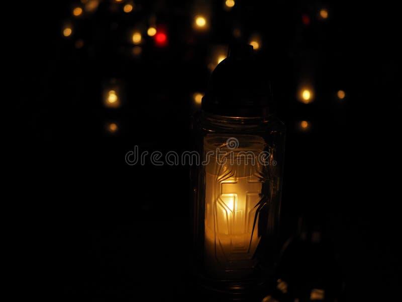 Quema de las velas blancas y coloridas en un cementerio en la noche de todos los santos, luces anaranjadas imagen de archivo libre de regalías