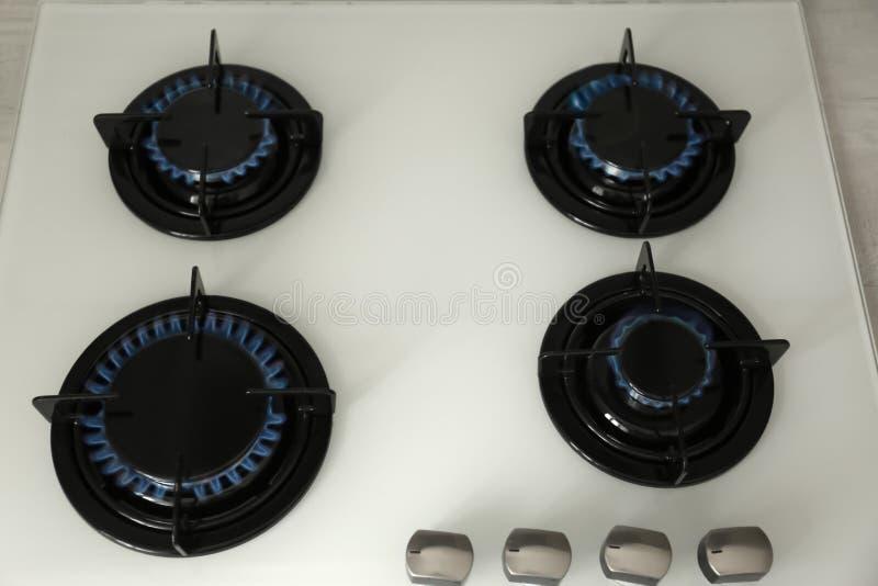 Quemadores de gas con la llama azul en estufa moderna foto de archivo