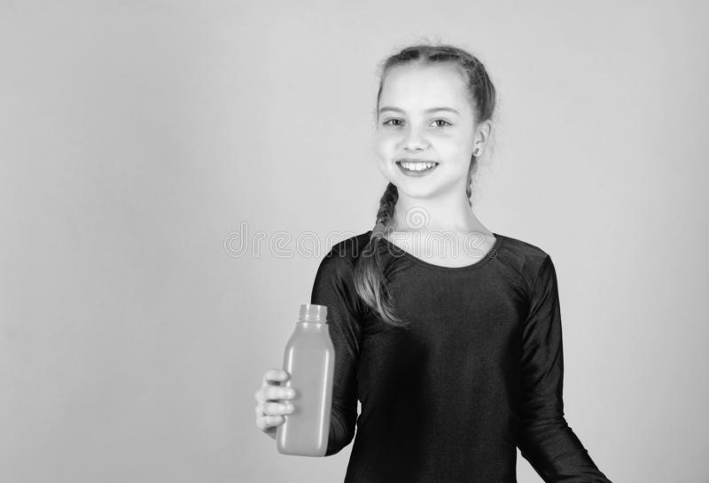 Quench thirst. Child feel thirst after sport training. Kid cute girl gymnast sports leotard hold bottle for drink. Water. Balance and hard gym training. Drink stock image