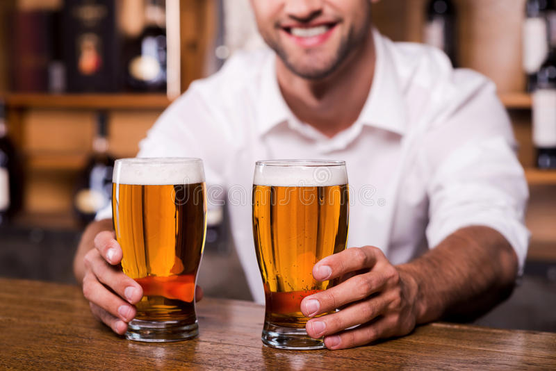 Quench your thirst!. Close-up of handsome young male bartender in white shirt stretching out glasses with beer and smiling while standing at the bar counter stock photos