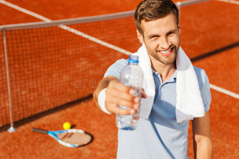 Quench your thirst!. Happy young man in polo shirt and towel on shoulders stretching out bottle with water while standing on tennis court stock photos