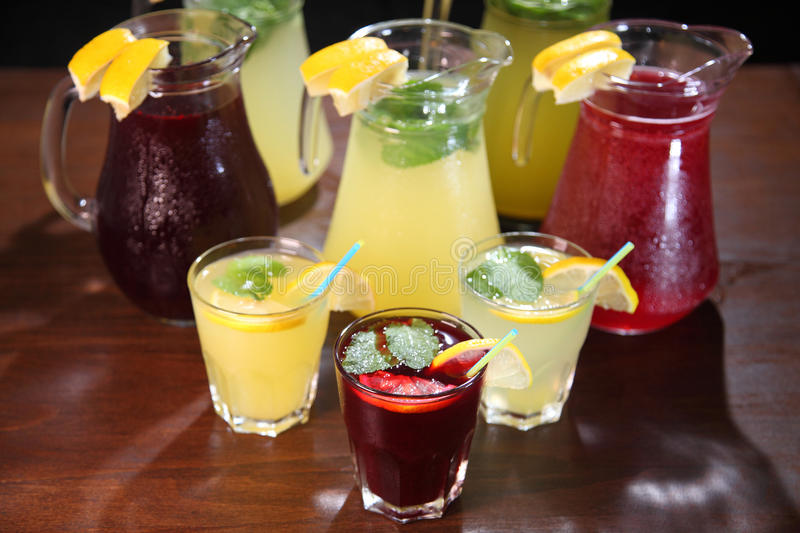 Quenching thirst and refreshing drinks. Cold lemonades. Lemonade. Morse. Compote. Lemonade in the jug and lemons with mint on the table indoor. Quenching thirst stock photography