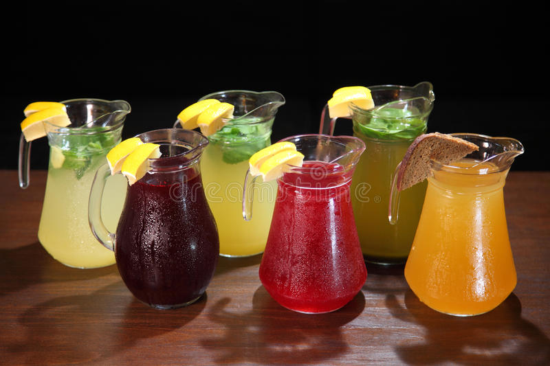 Quenching thirst and refreshing drinks. Cold lemonades. Lemonade. Morse. Compote. Lemonade in the jug and lemons with mint on the table indoor. Quenching thirst royalty free stock photo