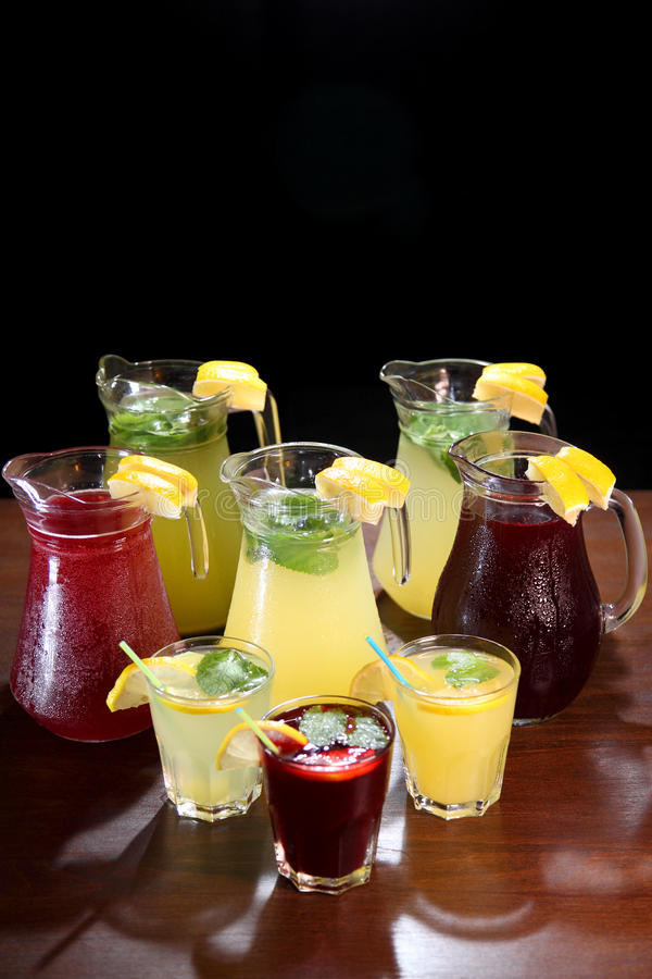 Quenching thirst and refreshing drinks. Cold lemonades. Lemonade. Morse. Compote. Lemonade in the jug and lemons with mint on the table indoor. Quenching thirst stock images