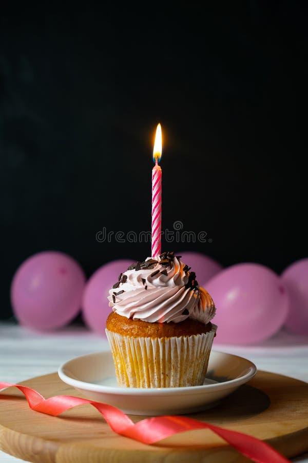 Queque brithday feliz com uma vela em um fundo preto fotografia de stock