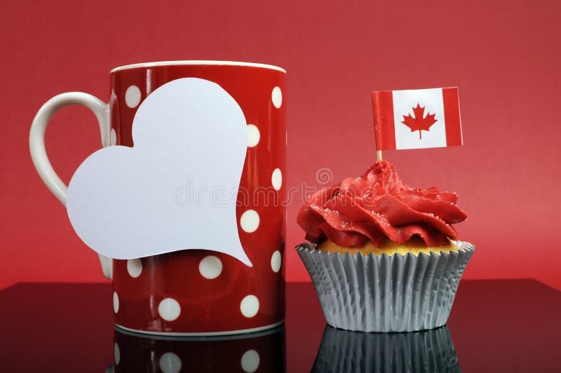 Queque canadense do tema vermelho e branco com bandeira da folha de bordo e a caneca vermelha do coffe do às bolinhas imagem de stock