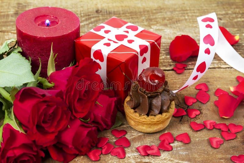 Queque com a cereja na frente do ramalhete de rosas vermelhas foto de stock